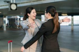Duas mulheres se encontram e se abraçam para estudar juntas 3 Formas de Dizer 'Esperar' Em Inglês.