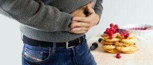 homem mostra que está com dor de barriga após comer doce