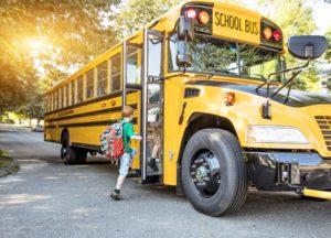 garoto entrando no ônibus da escola